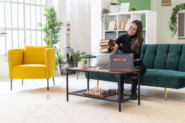 Smiling young woman collecting books in box on coffee table at loft apartment