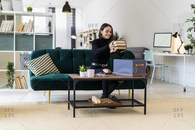 Smiling beautiful woman collecting books in box on coffee table at loft apartment