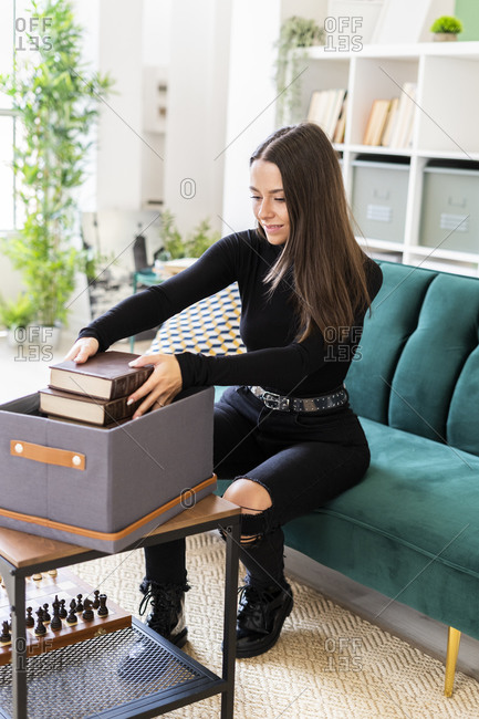 Beautiful female brunette collecting books in box while sitting on sofa at loft apartment
