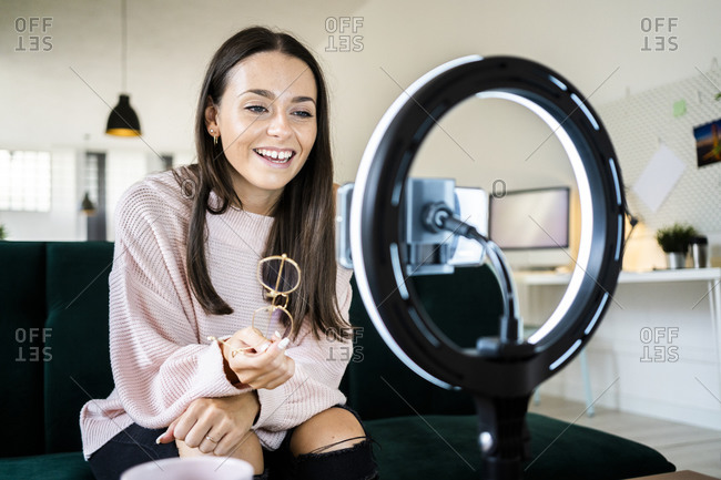 Smiling beautiful female vlogger filming through smart phone at home