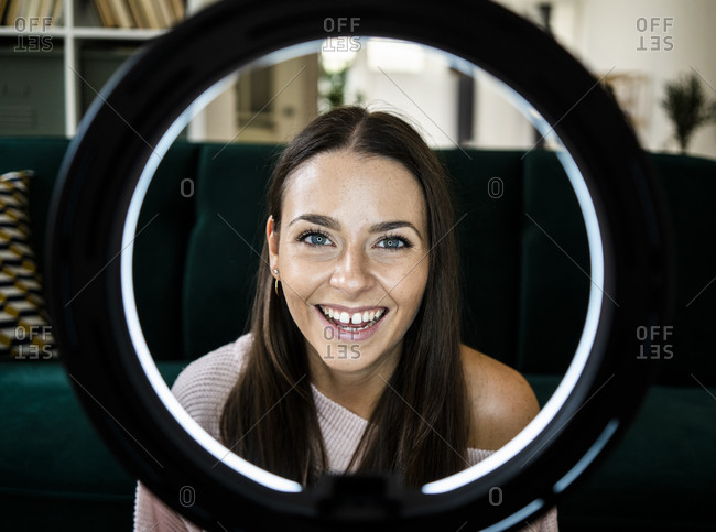 Happy female influencer with illuminated lighting equipment at home