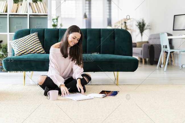 Smiling beautiful young woman sitting with note pads and coffee cup on carpet against sofa at home