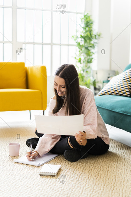Smiling young woman writing in note pad while sitting with coffee cup on carpet against sofa at loft apartment