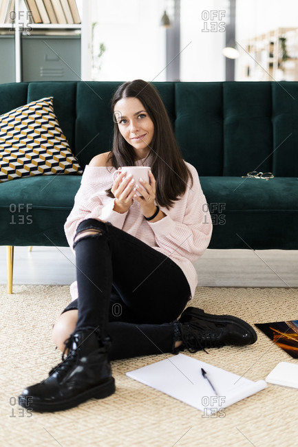 Beautiful young woman sitting with coffee cup and note pads on carpet against sofa at home