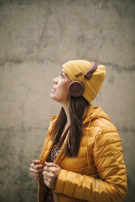 Thoughtful woman in warm clothing listening music through headphones while standing by wall