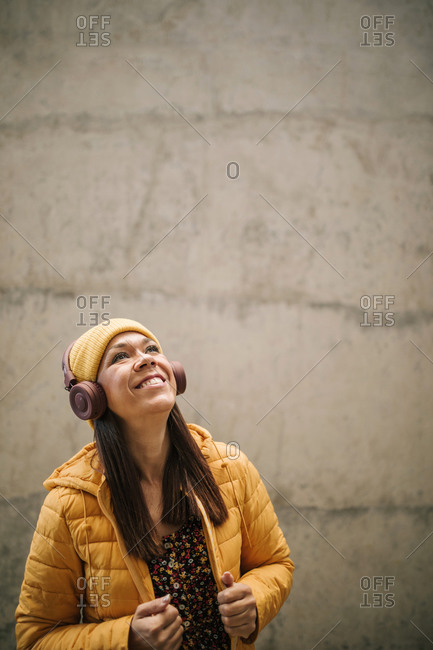 Happy mature woman in warm clothing looking up while listening music through headphones against wall