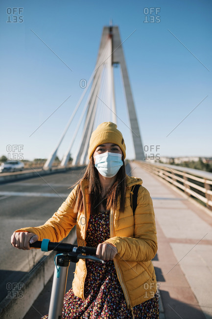 Woman in protective face mask with electric scooter on bridge in city during COVID-19