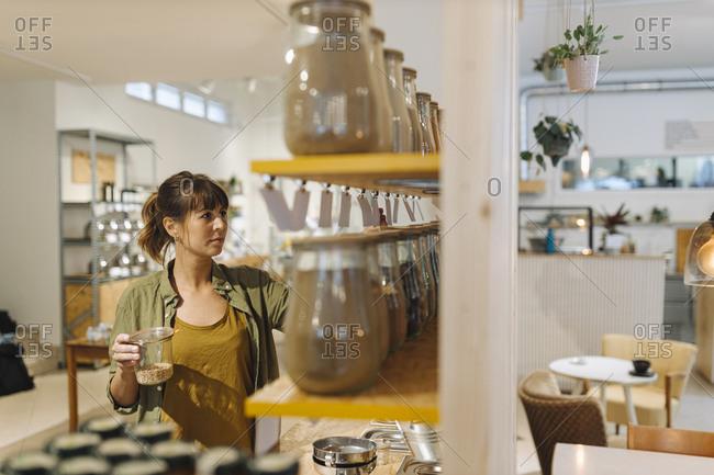 Female entrepreneur arranging glass jar in cafe