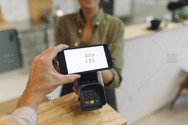 Cropped hand of customer doing contactless payment with smart phone while female owner holding credit card reader at checkout in coffee shop