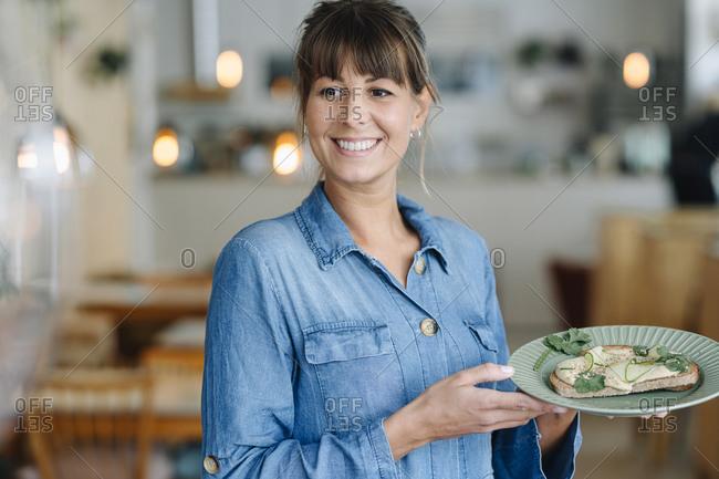 Smiling female entrepreneur holding bruschetta while standing in cafe