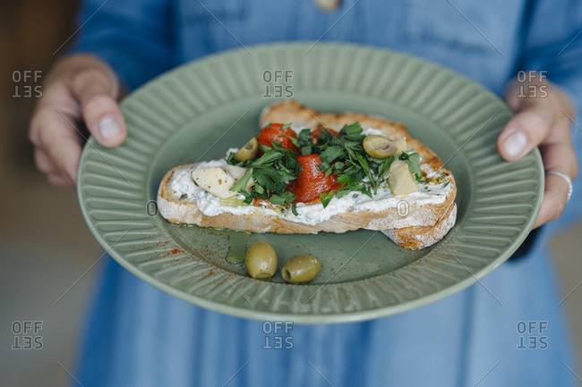 Midsection of businesswoman holding bruschetta while standing in cafe