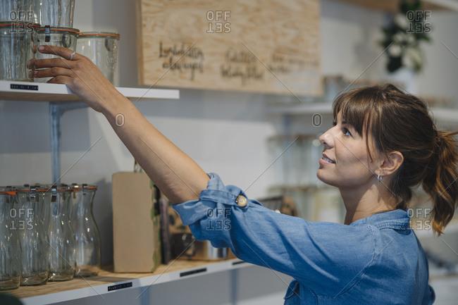 Businesswoman arranging glass jar on shelf in cafe