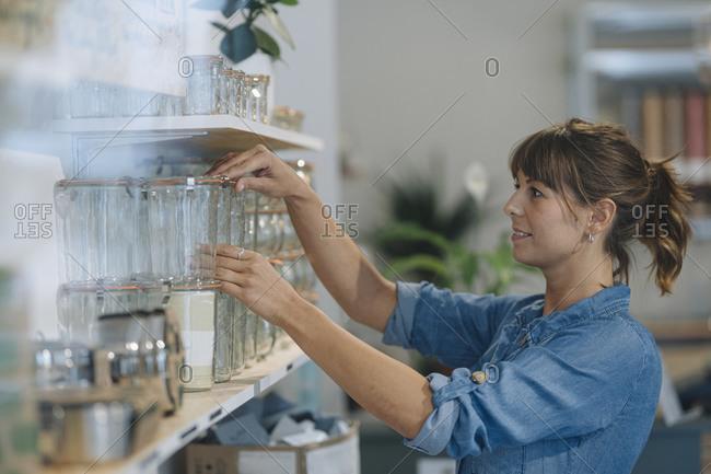 Young female entrepreneur arranging glass jar on shelf in cafe