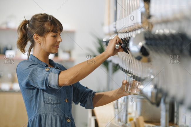 Young businesswoman filling grain in glass jar while standing in cafe