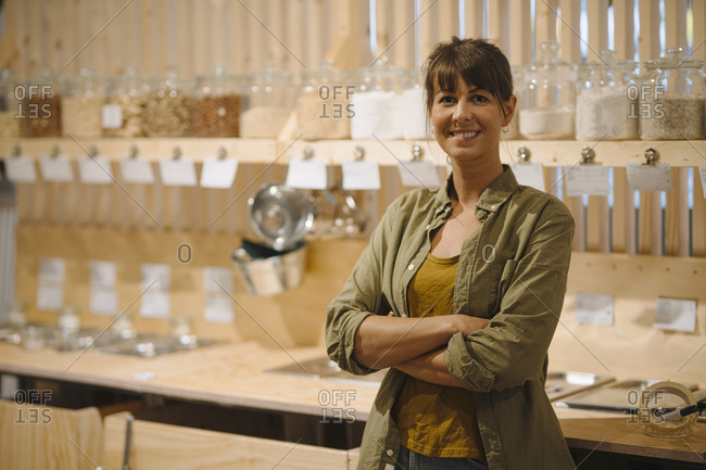 Smiling businesswoman with arms crossed standing against glass jar in cafe