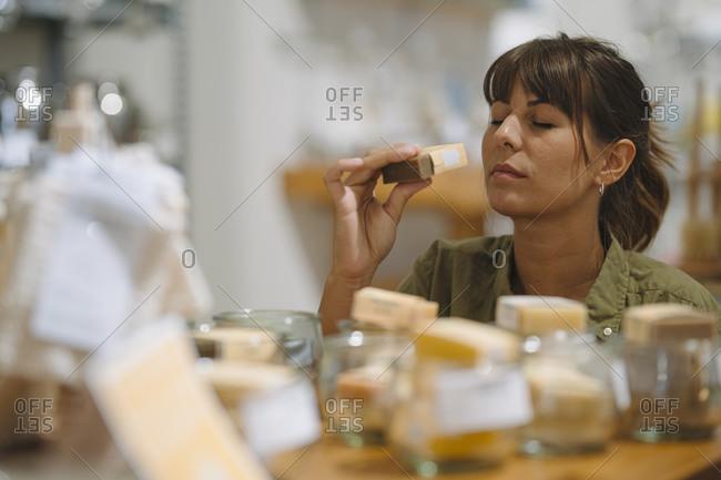 Female entrepreneur smelling soap in coffee shop