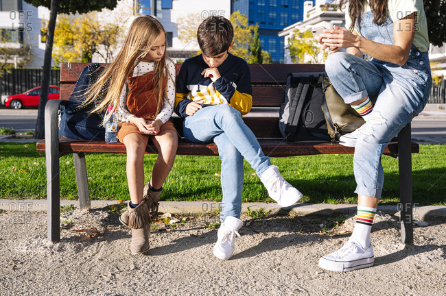 Low section of mother with kids using smart phone while sitting on bench in public park during sunny day
