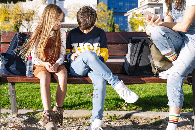 Low section of mother with smiling kids using smart phone while sitting on bench in public park