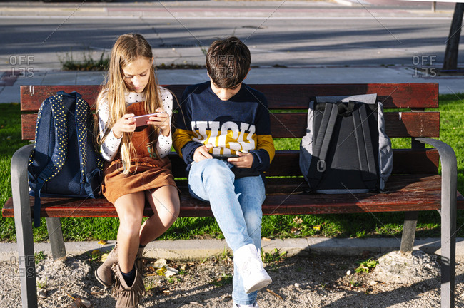 Sibling using smart phone while sitting on bench in public park during sunny day