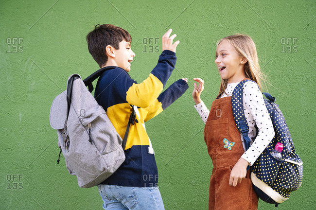 Brother and sister laughing doing high five while standing against green wall on sunny day