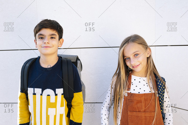 Brother and sister standing against white wall on sunny day
