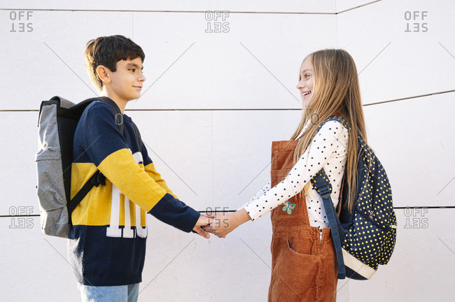 Happy brother and sister holding hands while standing by wall on sunny day