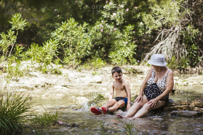 Grandmother and grandson talking while sitting on stone in river at forest