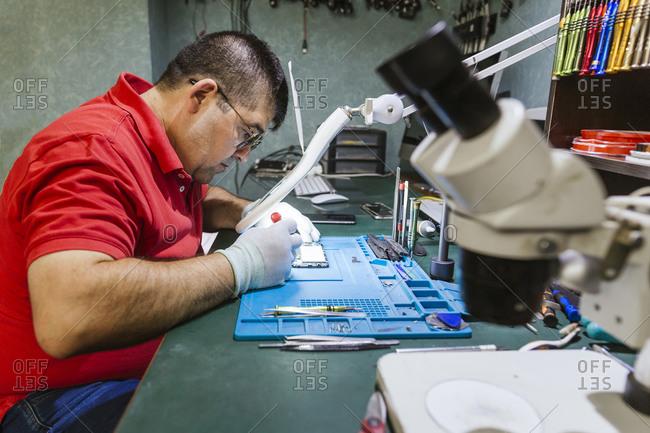 Engineer looking at broken smart phone through magnifying glass in electronics repair shop