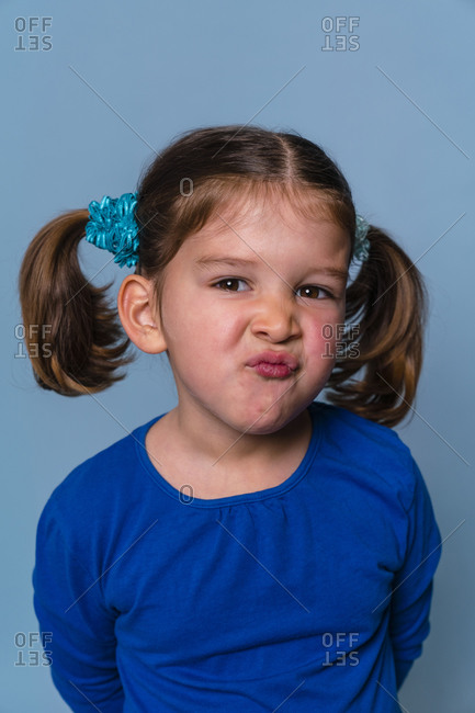 Girl making angry puckering face while standing against blue background