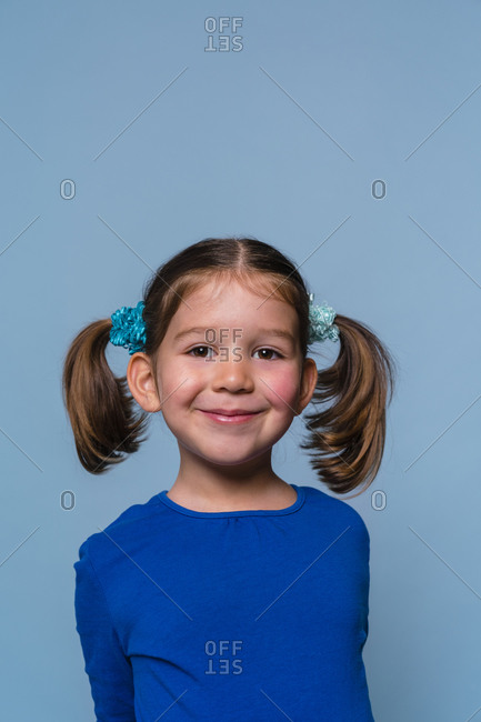 Smiling girl standing with hands behind back against blue background
