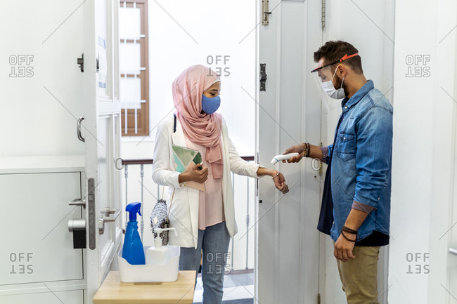 Man checking temperature of woman while standing at office entrance