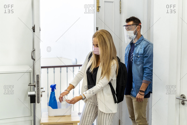 Blond woman wearing face mask washing hands while standing with coworker in background at office