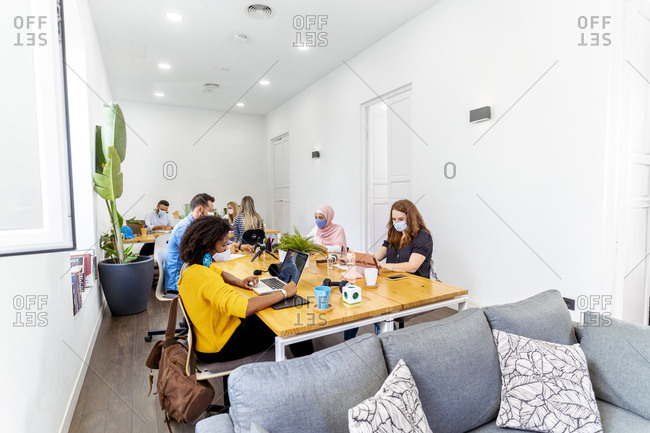 Business people with face mask sitting at social distance while sitting at office