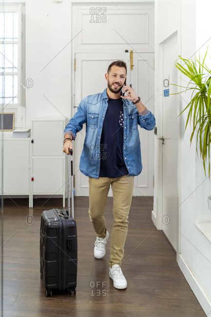 Mid adult man talking on mobile phone while walking with luggage at office
