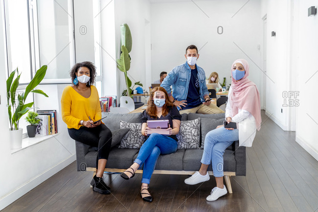 Employees wearing face mask maintaining social distance while sitting with coworker in background at office during COVID-19