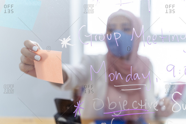 Young woman wearing face mask putting adhesive note on glass wall while standing at office