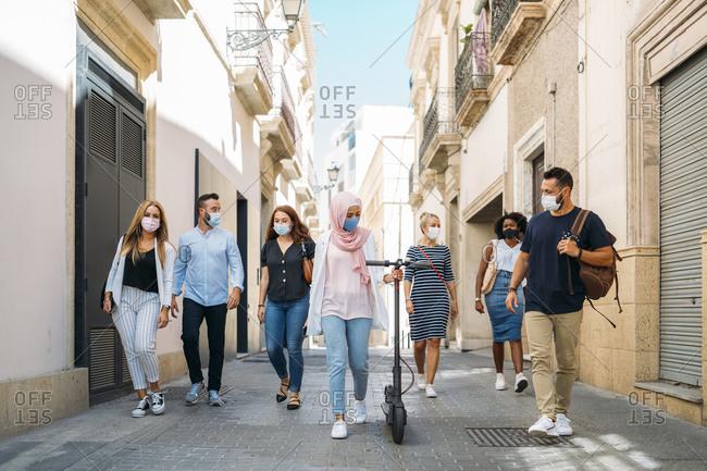 Friends wearing face masks walking on street in city
