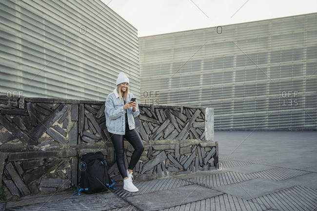 Smiling young woman text messaging through smart phone while leaning on retaining wall