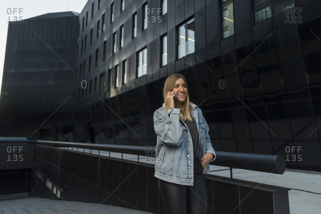 Smiling young woman talking on smart phone while standing outside modern building