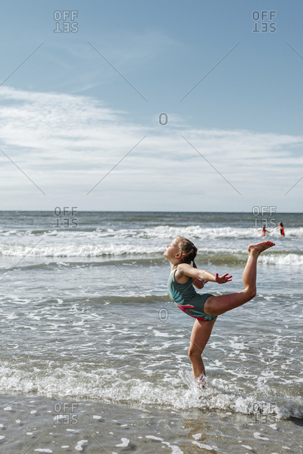 Girl doing gymnastics while standing in water at beach on sunny day