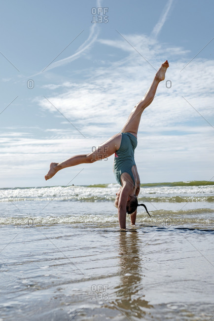 Girl doing gymnastics in sea during sunny day
