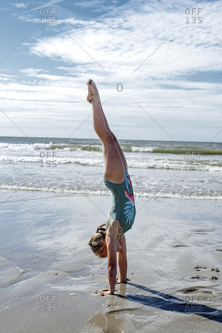 Girl gymnast doing upside on sand at beach during sunny day