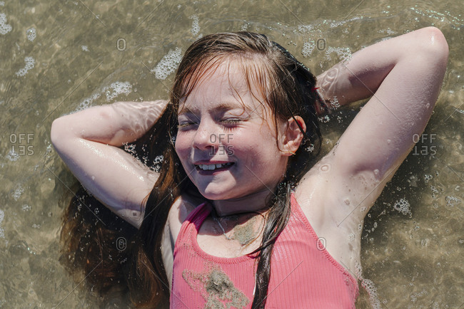Girl lying on back with hands behind head in water during sunny day