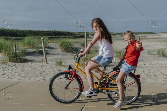 Girl taking younger sibling on bicycle at beach during sunny day