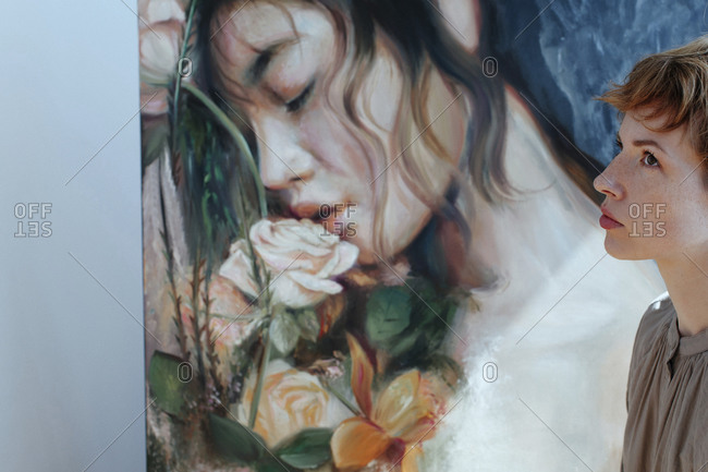 Thoughtful female artist by canvas painting in art studio
