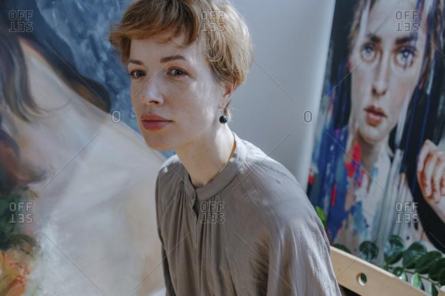 Female artist looking away against painting in art studio