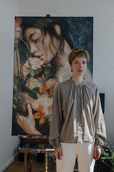 Confident female artist standing against painting in art studio