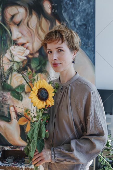 Smiling female artist holding sunflower while standing against artwork