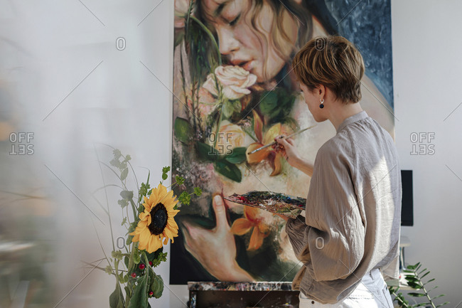 Mid adult female artist painting on canvas in studio
