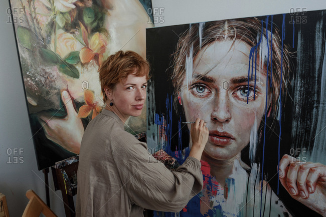 Female artist painting on canvas in studio